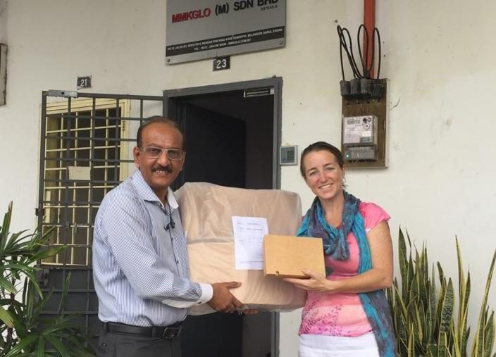 Charity liaison handing over box
